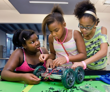 Destnee Walton, 12, from left, Martayllia Copes, 10, and Jordan Miller, 11, all of Kansas City, assemble a robot, July 20, at Science City in Kansas City's Union Station. Courtesy of mctcampus.com
