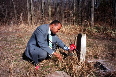 Historian Currie Ballard examines a grave at Beulahland Cemetery near Langston, Oklahoma. Several towns in Oklahoma that were among the settlements built by African-Americans are hoping looking to draw tourists based on their history.