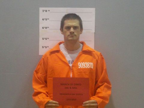 Joshua Robison poses for a mug shot for the hail and bail fundraiser. Photo by: Marisa Caban