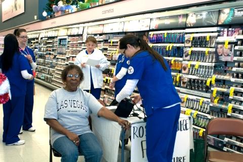 Nursing Student taking a community member's blood pressure.