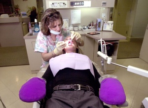 A patient gets their teeth cleaned and screened at a dentist's office.