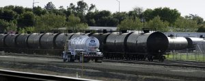 Recently filled, a tanker truck drives past railway cars containing crude oil. Photo Courtesy of MCTCampus